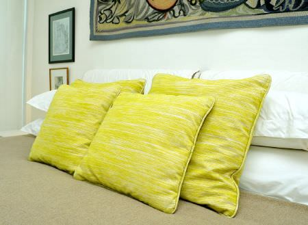 Christopher Farr -  Printed Indoor Fabric Collection - Lime green scatter cushions on a bed with a light brown blanket and white pillows, with framed pictures on the wall
