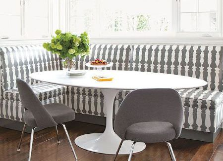 Christopher Farr -  Printed Indoor Fabric Collection - A large oval shaped white table with L-shaped bench seating with a grey and white candlestick print, and two grey chairs