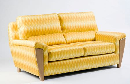 Christopher Farr -  Printed Indoor Fabric Collection - A retro style sofa featuring some wood detail amongst a bright mustard yellow and pale yellow patterned cover