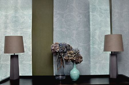 Christopher Farr -  Printed Indoor Fabric Collection - Two grey lamps with brown shades, glass and sky blue vases, in front of a khaki and patterned paleblue-grey backdrop