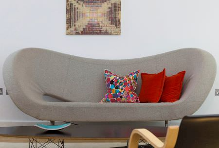 Christopher Farr -  Woven Indoor Fabric Collection - A stylish modern curved grey sofa with plain bright red and patterned cushions, a wooden table, a blue bowl and an armchair