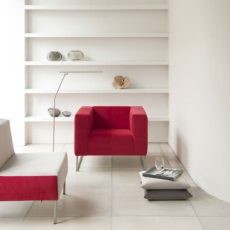 Clarke and Clarke -  Altea Fabric Collection - Boxy red armchair with similar white and red chair, with grey scatter cushions and a very simple floor lamp made from a single tube of metal