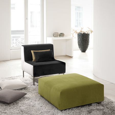 Clarke and Clarke -  Altea Fabric Collection - Simple black suede effect chair with white sides, square green footstool, fluffy grey rug, scatter cushions, white table and large grey urn
