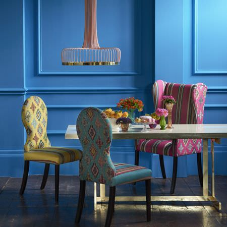 Clarke and Clarke -  Anatolia Fabric Collection - A modern curved wood and gold ceiling light, a metal dining table, and pink, blue and yellow striped and patterned chairs