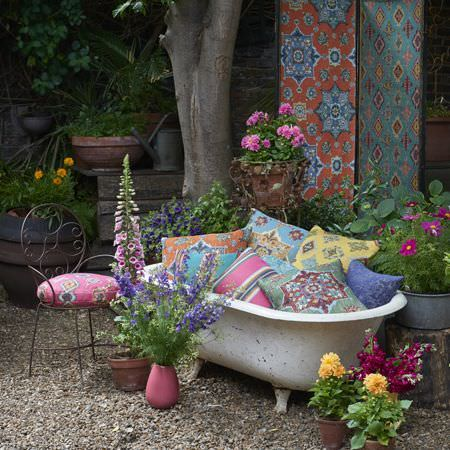 Clarke and Clarke -  Anatolia Fabric Collection - A metal chair with a pink seat, and an outdoor bath with pink, blue, yellow, green and orange patterned and striped cushions