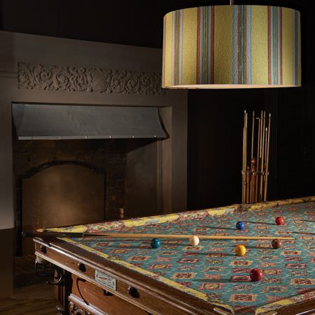 Clarke and Clarke -  Anatolia Fabric Collection - An eye-catching yellow, turquoise and salmon pink pattern on a snooker table, witha large, matching, striped lampshade