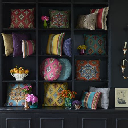 Clarke and Clarke -  Anatolia Fabric Collection - A black wall unit filled with different shaped plain, striped and patterned cushions in red, pink, yellow, blue and orange