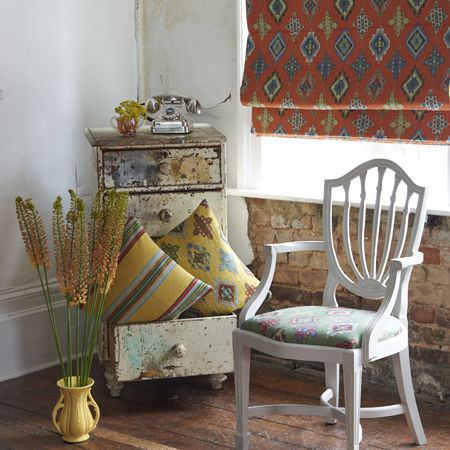 Clarke and Clarke -  Anatolia Fabric Collection - A white chair with a green seat, yellow striped and patterned cushions in a distressed chest of drawers,and an orange blind