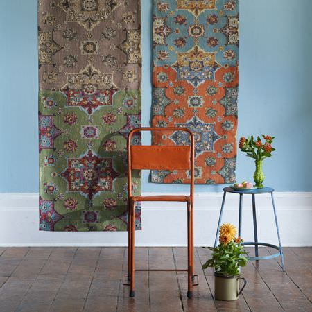 Clarke and Clarke -  Anatolia Fabric Collection - An orange metal chair, a round blue table, with 2 hanging strips of patterned fabric in brown, green, red, blue and orange