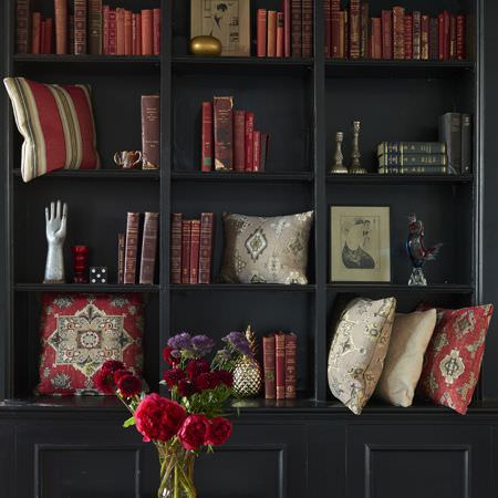 Clarke and Clarke -  Anatolia Fabric Collection - A black wood wall unit with vintage books,red and cream coloured patterned and striped cushions, a vase and flowers
