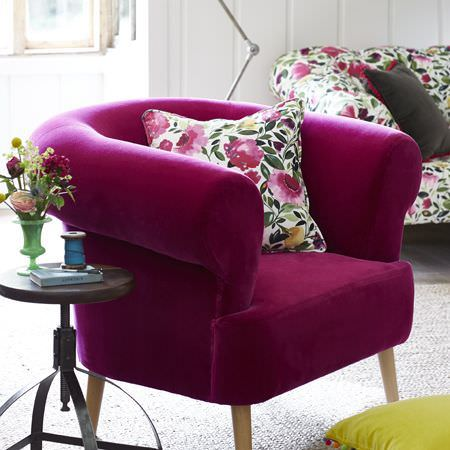 Clarke and Clarke -  Artbook by Kim Parker Fabric Collection - A bright fuschia armchair with a pink, white and dark green sofa and cushion,a citrus cushion and a small round table