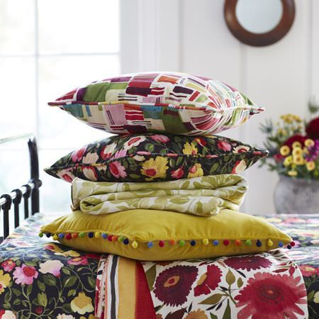Clarke and Clarke -  Artbook by Kim Parker Fabric Collection - A stack of floral, patterned and plain cushions and folded fabrics in black, dark green, citrus, dark red, pink and white