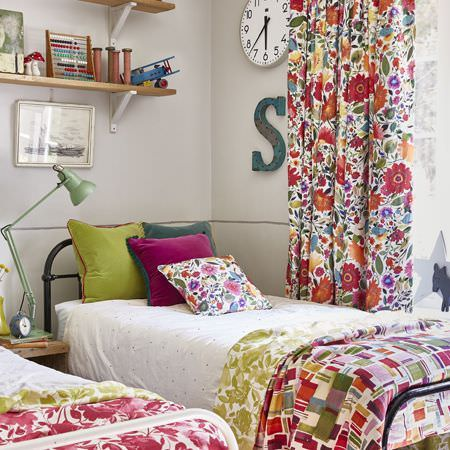 Clarke and Clarke -  Artbook by Kim Parker Fabric Collection - Black beds with white sheets, bright, plain cushions, and multicoloured floral and patterned curtains, throws and a cushion