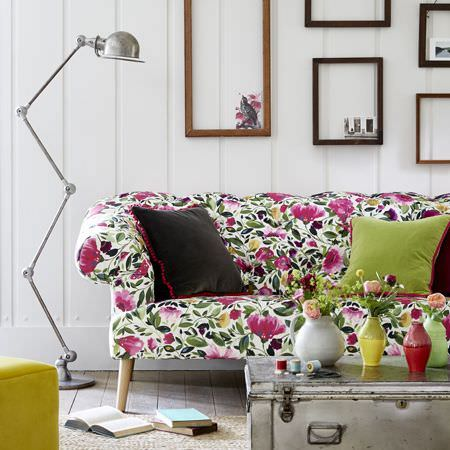 Clarke and Clarke -  Artbook by Kim Parker Fabric Collection - A large floral sofa, plain citrus and slate grey cushions,a metal chest, an anglepoise floor lamp, and empty frames