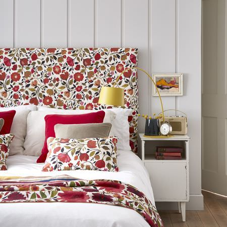 Clarke and Clarke -  Artbook by Kim Parker Fabric Collection - A bed with white bedding, 4 plain red and grey cushions, and red, whiteand green floral cushions, a throw and a headboard