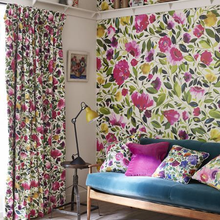 Clarke and Clarke -  Artbook by Kim Parker Fabric Collection - Large pink, green, yellow and white florals on walls, curtains and cushions, with a teal sofa with a wood frame, and a lamp