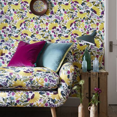 Clarke and Clarke -  Artbook by Kim Parker Fabric Collection - Plain fuschia and dusky blue cushions with a sofa and wallpaper, both covered with large citrus, green and purple florals