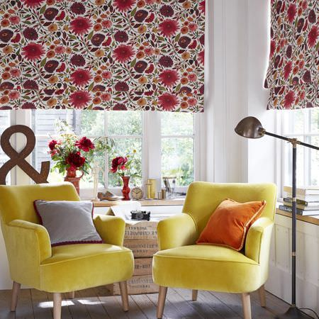 Clarke and Clarke -  Artbook by Kim Parker Fabric Collection - Two canary yellow armchairs with plain orange and grey cushions, floral blinds made in dark shades of red, and a floor lamp