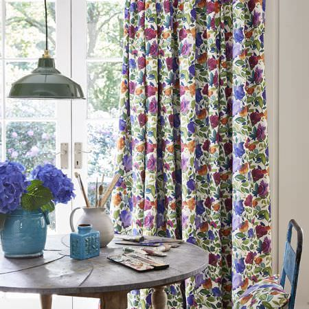 Clarke and Clarke -  Artbook by Kim Parker Fabric Collection - Purple, green, orange and maroon floral curtains, with a round wood table, a blue chair, a cushion and a round, blue vase