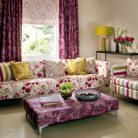 Clarke and Clarke -  Artiste Fabric Collection - A patchy purple and grey footstool and curtains, with a large floral sofa and a striped armchair in white, purple and green
