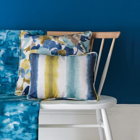 Clarke and Clarke -  Artiste Fabric Collection - White and wood ombre effect chair with patchy aqua blue fabric and two cushions in white, olive green, dusky blue and navy