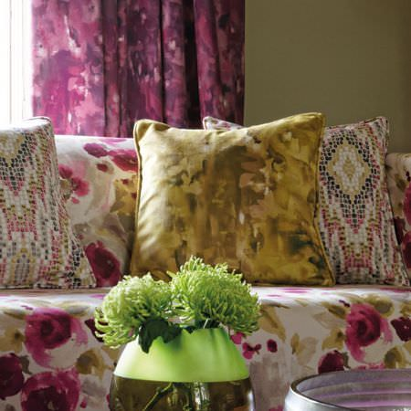 Clarke and Clarke -  Artiste Fabric Collection - A purple, green and white floral sofa with patchy yellow-green and patterned cushions, and curtains made in purples and pinks
