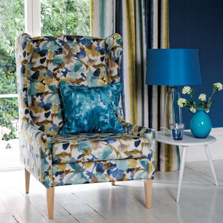 Clarke and Clarke -  Artiste Fabric Collection - A blue, green and white floral armchair with a patchy blue cushion, striped curtains, a white table and a Royal blue lamp
