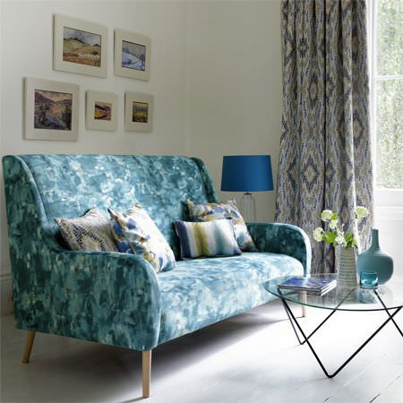 Clarke and Clarke -  Artiste Fabric Collection - A patchily coloured blue sofa with patterned and striped cushions, patterned curtains, a glass and metal table and vases