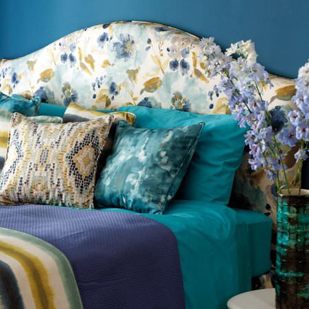 Clarke and Clarke -  Artiste Fabric Collection - Floral headboard with plain and striped bedding and patterned cushions all in shades of white, green and aqua blue