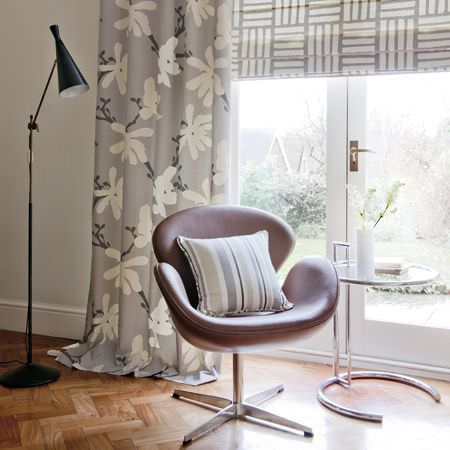 Clarke and Clarke -  Astrid Fabric Collection - A grey roman blind with a white stripe grid, a grey curtain with a modern white flower print, and a leather chair with a striped cushion