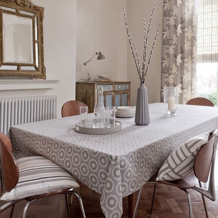 Clarke and Clarke -  Astrid Fabric Collection - A modern grey tablecloth with a white circular grid decoration, grey and white striped cushions, a grey curtain with a modern flower pattern