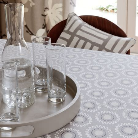 Clarke and Clarke -  Astrid Fabric Collection - A close up photo of a modern grey tablecloth with a circular pattern decoration and a pillow with a striped grid pattern