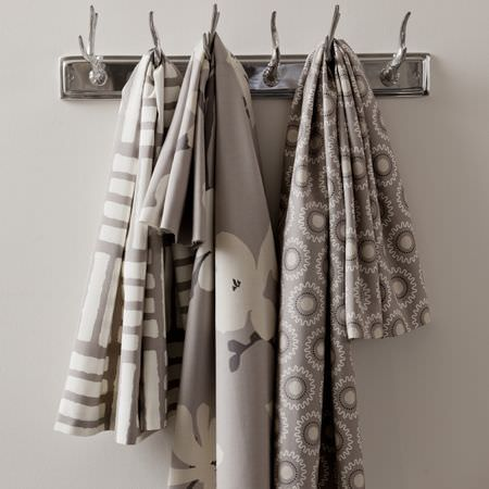 Clarke and Clarke -  Astrid Fabric Collection - Modern grey fabric decorated with flowers and circular grids and stripes, hanging on coat hangers, from the Astrid fabric collection