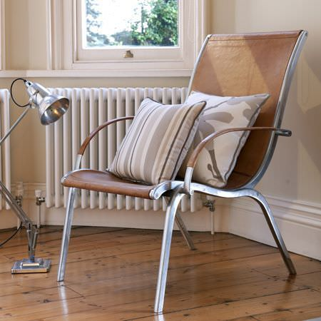 Clarke and Clarke -  Astrid Fabric Collection - A modern metal and leather chair with a grey and white striped cushion and a cushion with a modern grey flower decoration
