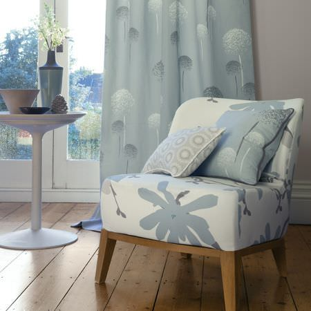 Clarke and Clarke -  Astrid Fabric Collection - Two cushions decorated with a circular grid and dandelions on top of a white upholstered chair, and a blue curtain with white dandelions