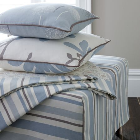 Clarke and Clarke -  Astrid Fabric Collection - Blue and white stripe upholstered footstool, with a white and blue cushions decorated with flowers and dark edging, and striped blankets