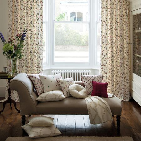 Clarke and Clarke -  Atmosphere Fabric Collection - A beige chaise longue with cream, red and grey leaf print curtains, matching patterned scatter cushions and a throw