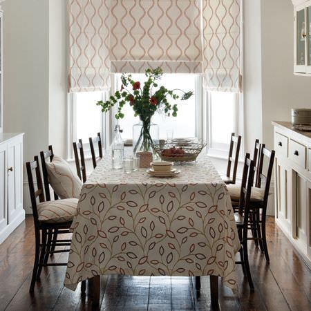 Clarke and Clarke -  Atmosphere Fabric Collection - A leaf print tablecloth with matching cushions and blinds in cream, red and grey, with a large table and eight chairs
