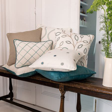 Clarke and Clarke -  Atmosphere Fabric Collection - Plain, patterned, checked and dotted cushions in off-white, turquoise and light brown, beside a jug on a dark wood bench