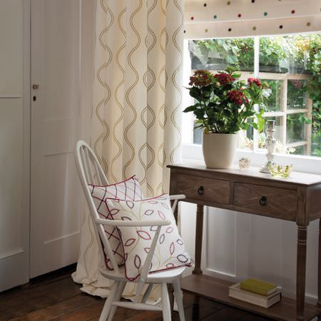 Clarke and Clarke -  Atmosphere Fabric Collection - A wooden side table with a white chair, cream and beige wavy line patterned curtains, a dotted blind and patterned cushions