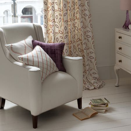 Clarke and Clarke -  Atmosphere Fabric Collection - Plain white armchair with wooden legs, three square patterned scatter cushions and red, grey and white leaf print curtains