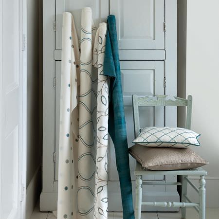 Clarke and Clarke -  Atmosphere Fabric Collection - Rolls of plain and patterned turquoise, white and grey fabrics with matching cushions and a light blue chair and wardrobe