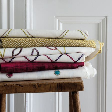 Clarke and Clarke -  Atmosphere Fabric Collection - A rustic wooden stool beneath a pile of folded fabrics with plain and patterned white, red, gold, purple and blue designs
