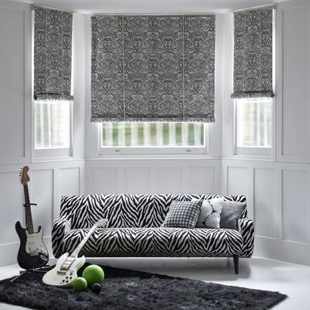 Clarke and Clarke -  Black and White Fabric Collection - Roman blinds with black and white floral design, zebra pattern on upholstered sofa and black and white cushions