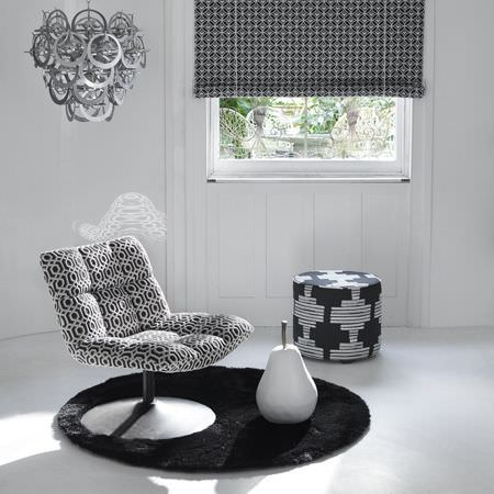 Clarke and Clarke -  Black and White Fabric Collection - Different modern black and white decorative designs on an ottoman, roman blinds and upholstered armchair