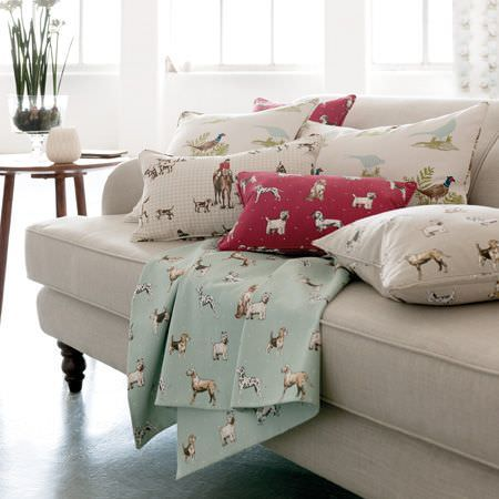 Clarke and Clarke -  Blighty Fabric Collection - Several different dog, pheasant and hunting print fabrics on cushions and throws, on a white sofa beside a round table