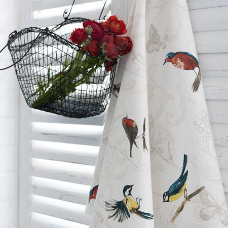 Clarke and Clarke -  Blighty Fabric Collection - A bunch of red flowers in a black metal basket, beside a swathe of white fabric featuring bright garden bird prints