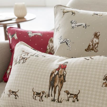 Clarke and Clarke -  Blighty Fabric Collection - A round wood table beside a beige sofa with three beige, red, brown and white cushions featuring dog and hunting prints