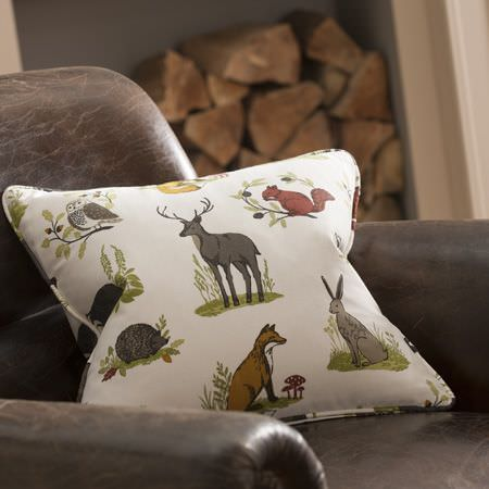 Clarke and Clarke -  Blighty Fabric Collection - A distressed dark leather armchair with a woodland themed cushion featuring foxes, deer, squirrels, hares and hedgehogs