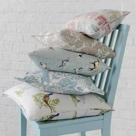 Clarke and Clarke -  Blighty Fabric Collection - A duck egg blue chair stacked with 5 scatter cushions featuring pastel coloured elephants, pheasants, dogs and patterns